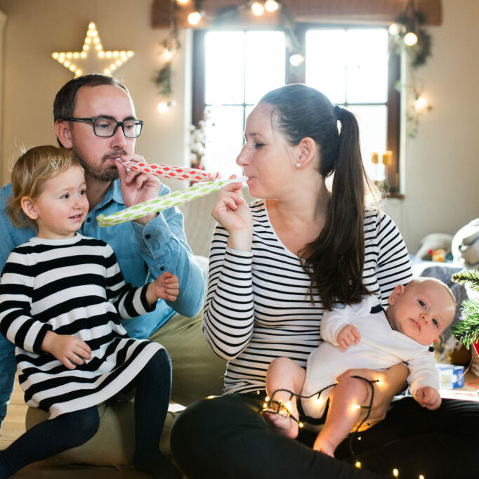 graphicstock-beautiful-young-parents-with-cute-daughter-and-baby-son-at-christmas-tree-blowing-party-whistles_BOvBzAhBGZ-2